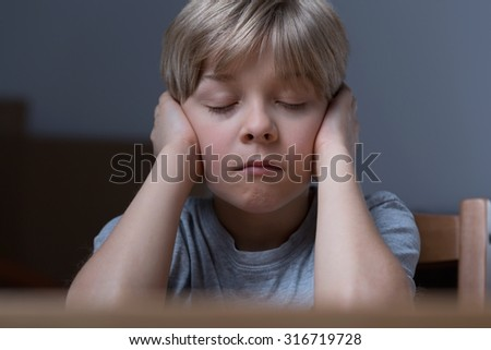 Little boy is scared because of his parents fighting - stock photo