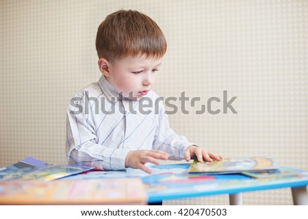 Little boy is sitting at the desk and read book