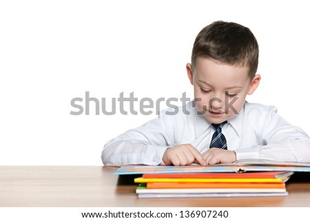 Little boy is sitting at the desk and read; on the white background