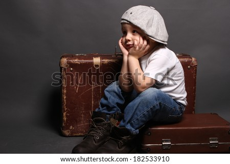 Little boy is sitting on big bag, boredom - stock photo