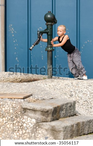 Little boy is using the water-pump - stock photo
