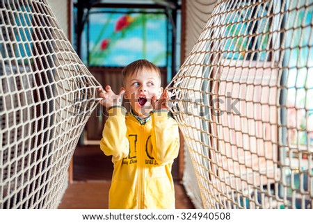 Little boy is very amazed in amusement park with rope walls - stock photo