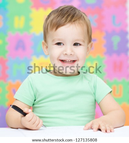 Little boy is writing on his copybook in preschool - stock photo
