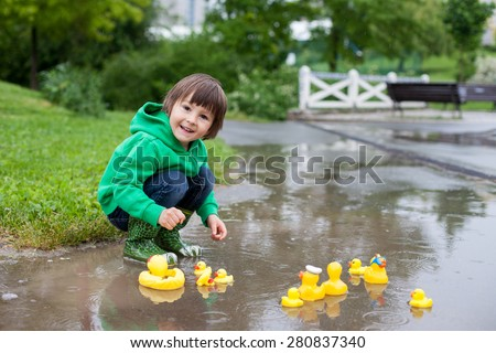 Little boy, jumping and playing in muddy puddles in the park, rubber ducks in the puddle - stock photo
