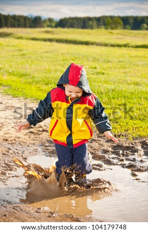 Little boy jumping in a mud puddle. - stock photo