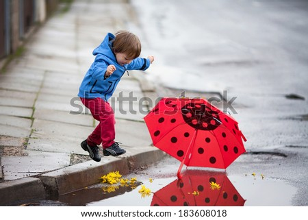 Little boy, jumping in muddy puddles - stock photo