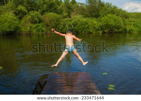 Little boy jumping into the water - stock photo