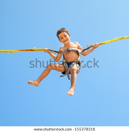 Little boy jumping on a trampoline on blue sky background  - stock photo