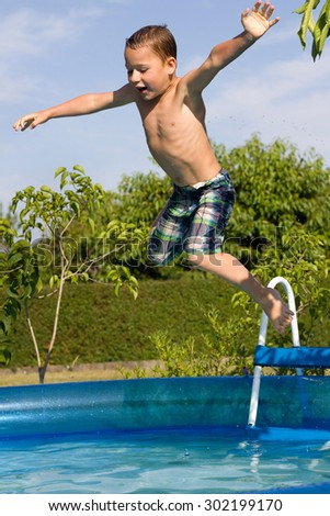 little boy jumps into the pool - stock photo