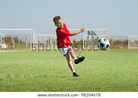 Little Boy Kicking at Goal - stock photo