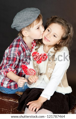 Little boy kissing beautiful smiling little girl.Valentine day