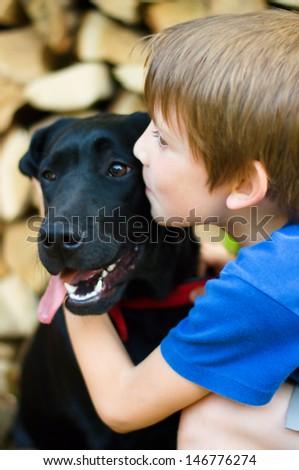 Little Boy Kissing Dog outdoors - stock photo