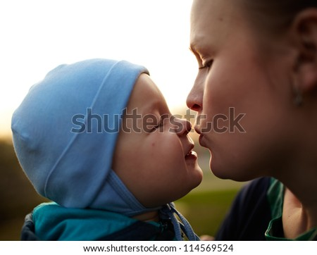 Little boy kissing his mom. Natural light, real colors, shallow DOF (prime 35mm L lense). - stock photo