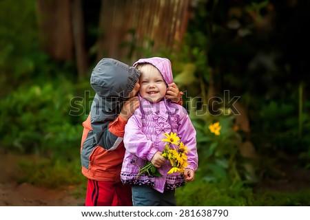 little boy kissing smiling little girl on her cheek, outdoor portrait - stock photo