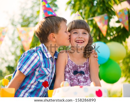 Little boy kissing with girl friend at birthday party - stock photo