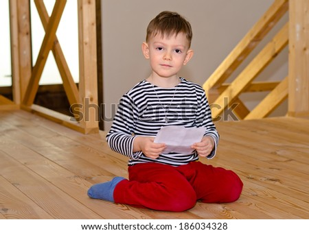 Little boy kneeling on the wooden floor in his socks reading a note or letter concentrating on the contents as he looks down