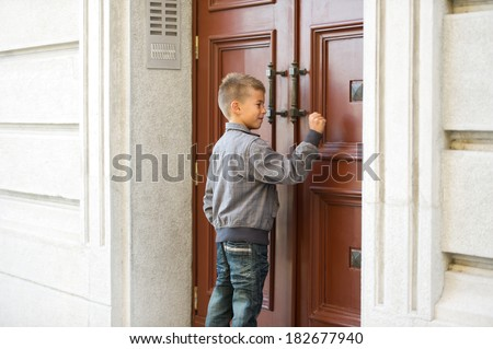 Little boy knocking the door - stock photo