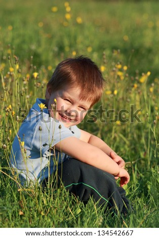 little boy laughing sitting in the grass