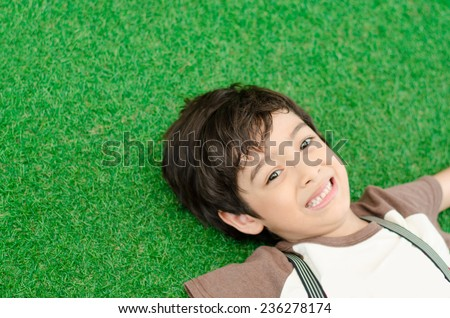 Little boy lay down on green grass - stock photo