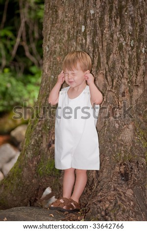 little boy leaning on a tree while grabbing ears and making a face - stock photo