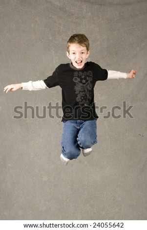 little boy leaping in air, over gray background - stock photo