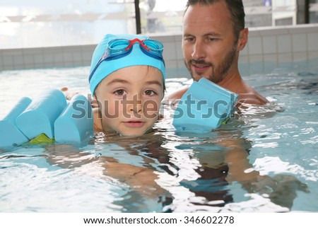 Little boy learning how to swim - stock photo