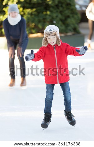 little boy learning ice skating and his mother watching and cheering up at outdoor skating rink, having winter vacation fun - stock photo