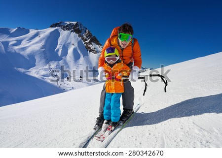 Little boy learns to ski on mountain resort with instructor helping to learn how to turn with mountain on background - stock photo