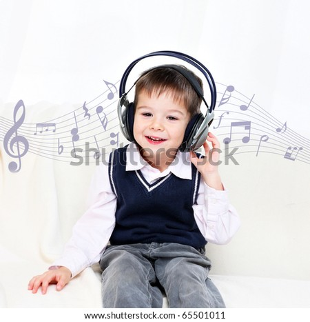 little boy listening to music in his earphones enjoying - stock photo