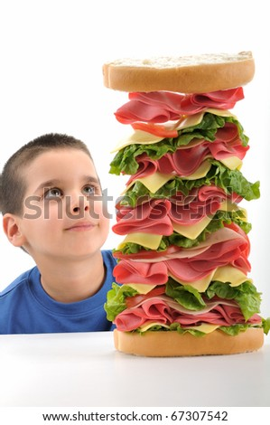 Little boy looking at big tower sandwich focused on sandwich isolated on white background. - stock photo