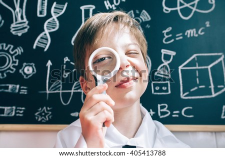 Little boy looking at camera through magnifying glass - stock photo