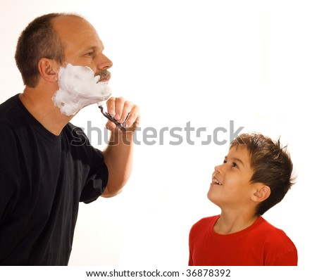 Little boy looking at his father shaving
