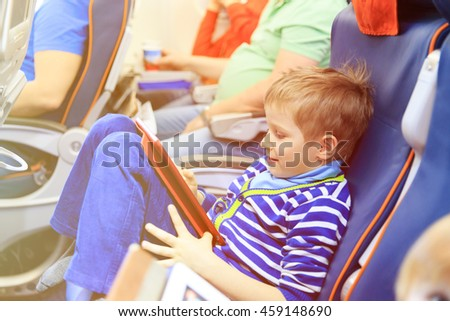 little boy looking at touch pad travelling by plane