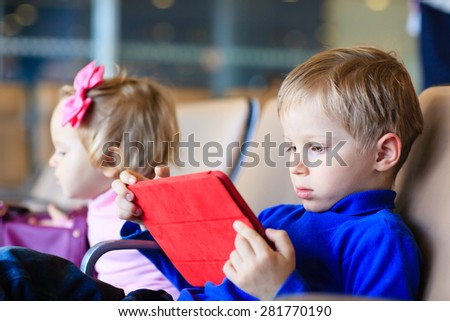 little boy looking at touch pad while travel in the airport