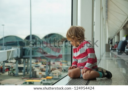 little boy looking at window sitting in the airport on the floor and waiting for his flight - stock photo