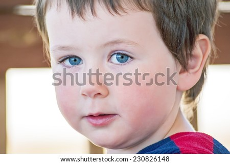 Little boy looking into the camera with pretty blue eyes. - stock photo