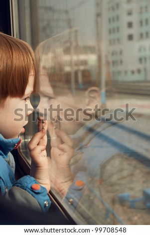 little boy looking out the train window - stock photo
