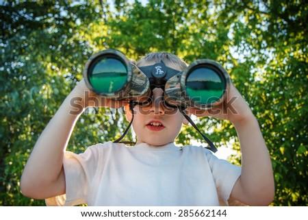 Little boy looking through binoculars on river bank - stock photo