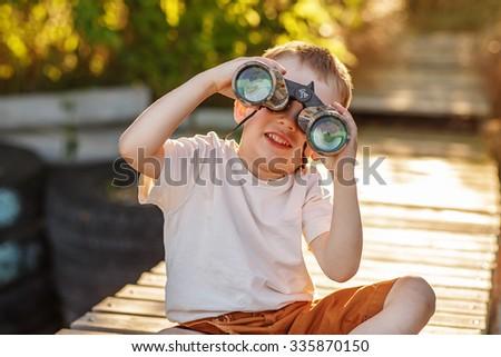 Little boy looking through binoculars sitting on the pier on river bank  - stock photo