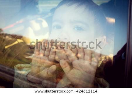 Little boy looking through window - stock photo