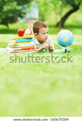 Little boy looking trough magnifying glass and exploring the globe in nature - stock photo