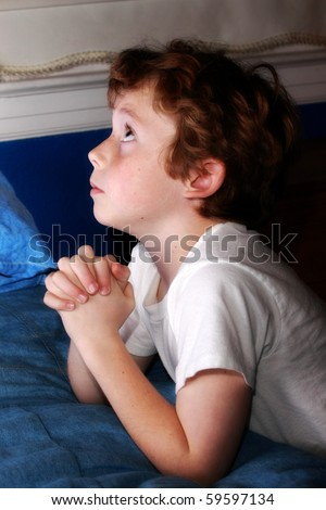 little boy looking up and praying - stock photo
