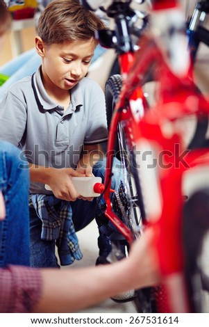 Little boy lubricating bike wheel chain - stock photo