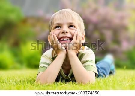 Little boy lying on a green grass - stock photo