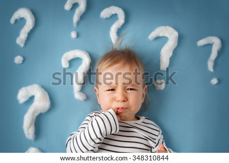 little boy lying on blue blanket with lots of question marks - stock photo