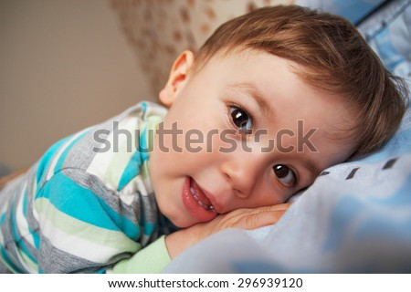 Little boy lying on the bed on his belly and looking at the camera, Natural light.