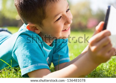 Little boy lying on the grass and using digital tablet - stock photo