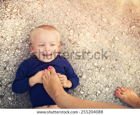 Little boy lying on the ground playing with this mother