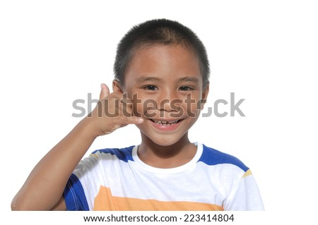 little boy making a call me gesture on white background