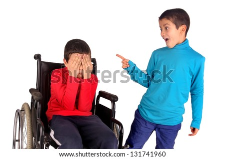 little boy making fun of friend in wheelchair - stock photo